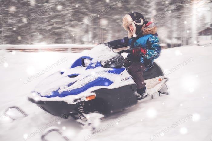 Junge fahren Schneemobil in einer Winterlandschaft