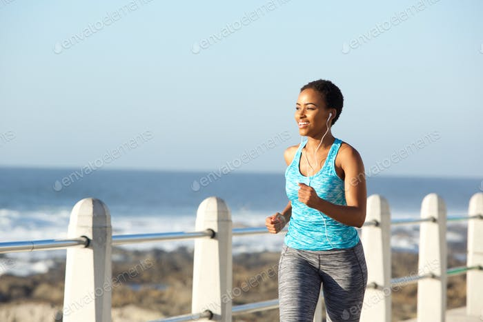 active young woman running by sea with earphones