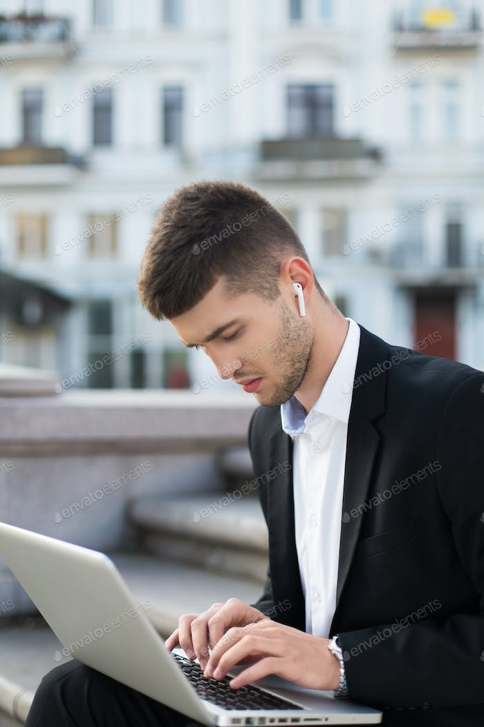Young pensive businessman in classic black suit with wireless ea