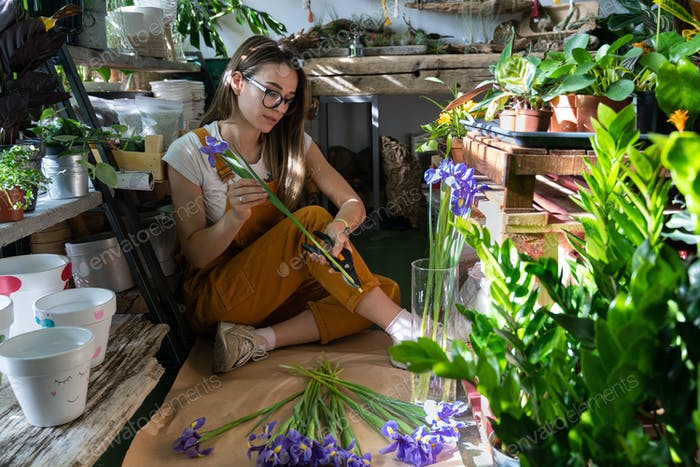 Florist woman cutting stem of irises flowers using secateurs sitting on the floor in flower store.