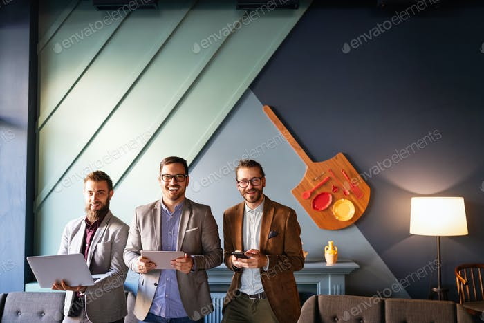 Group of confident happy business people holding digital devices
