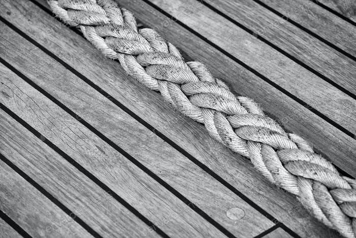 Thick rope on an old sailing ship wooden deck.