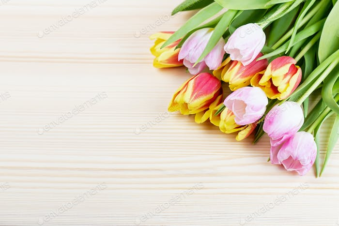 Colorful tulips bouquet on wooden background