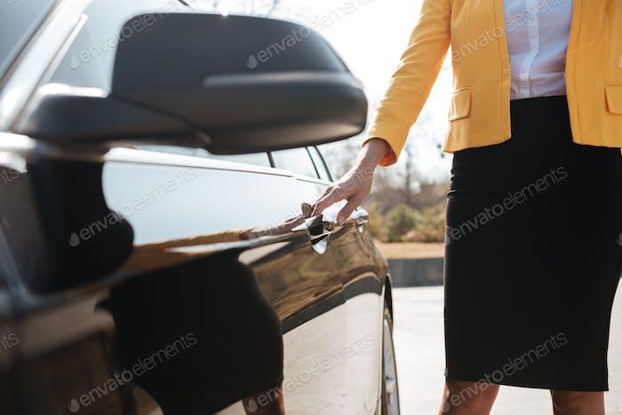 Businesswoman standing and opening the door of her car