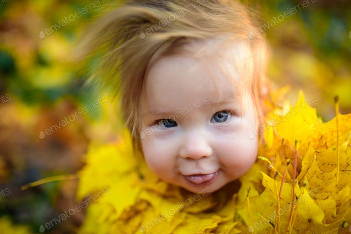 happy little girl laughs and plays outdoors. On the neck there is a necklace of autumn leaves.