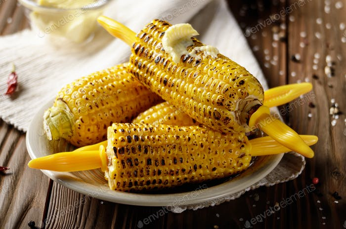 Wooden table with deep grilled sweet corn cobs under melting but