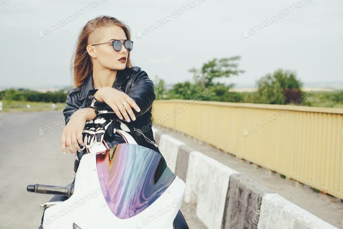 Beautiful woman posing with sunglasses on a motorbike