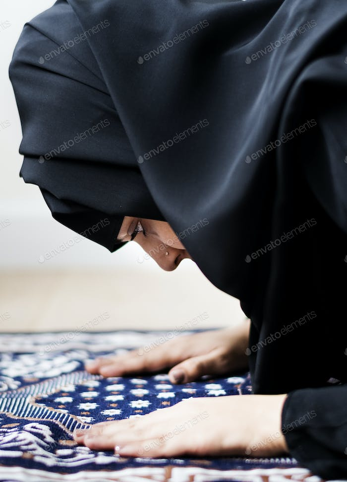 Muslim woman praying in the mosque during the Ramadan