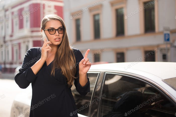 Young beautiful woman in black dress and sunglasses thoughtfully