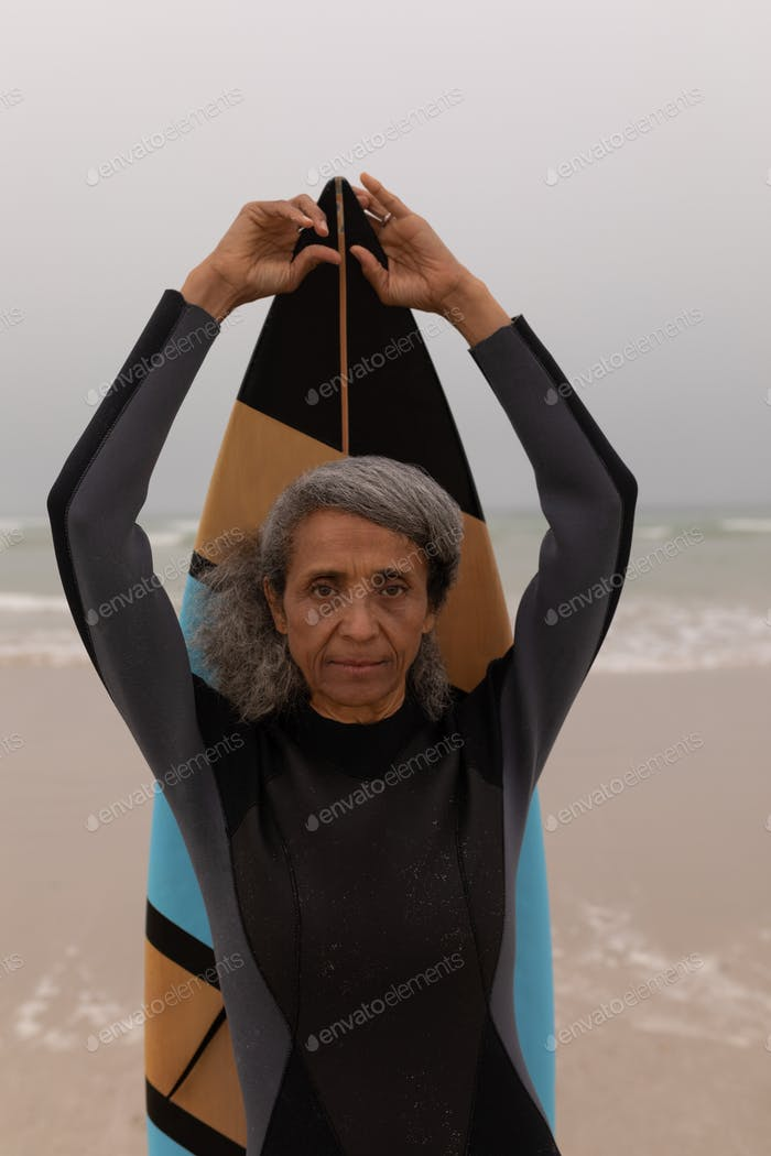 Front view of senior female surfer with arms up holding surfboard on the beach
