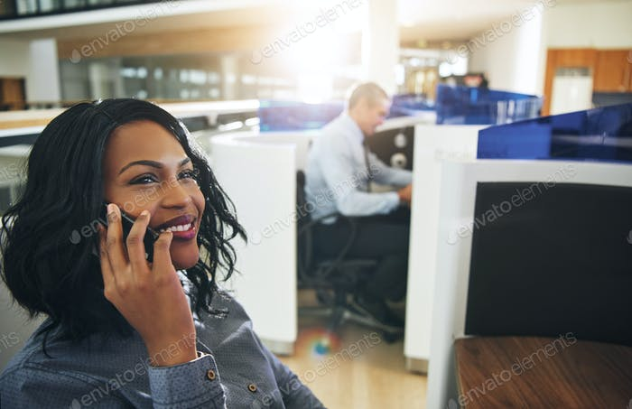 Pretty black female employee talking smartphone at workplace