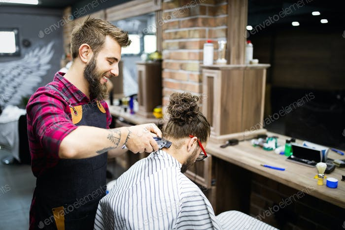 Young bearded man getting haircut by hairdresser with electric razor at barber shop