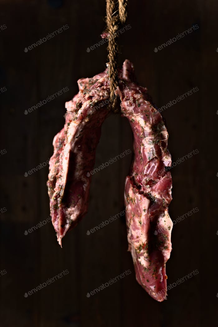 whole raw pork rib hanging in front of a wooden background