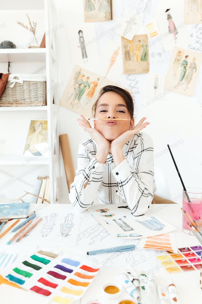 Funny lady fashion illustrator sitting at the table and joking