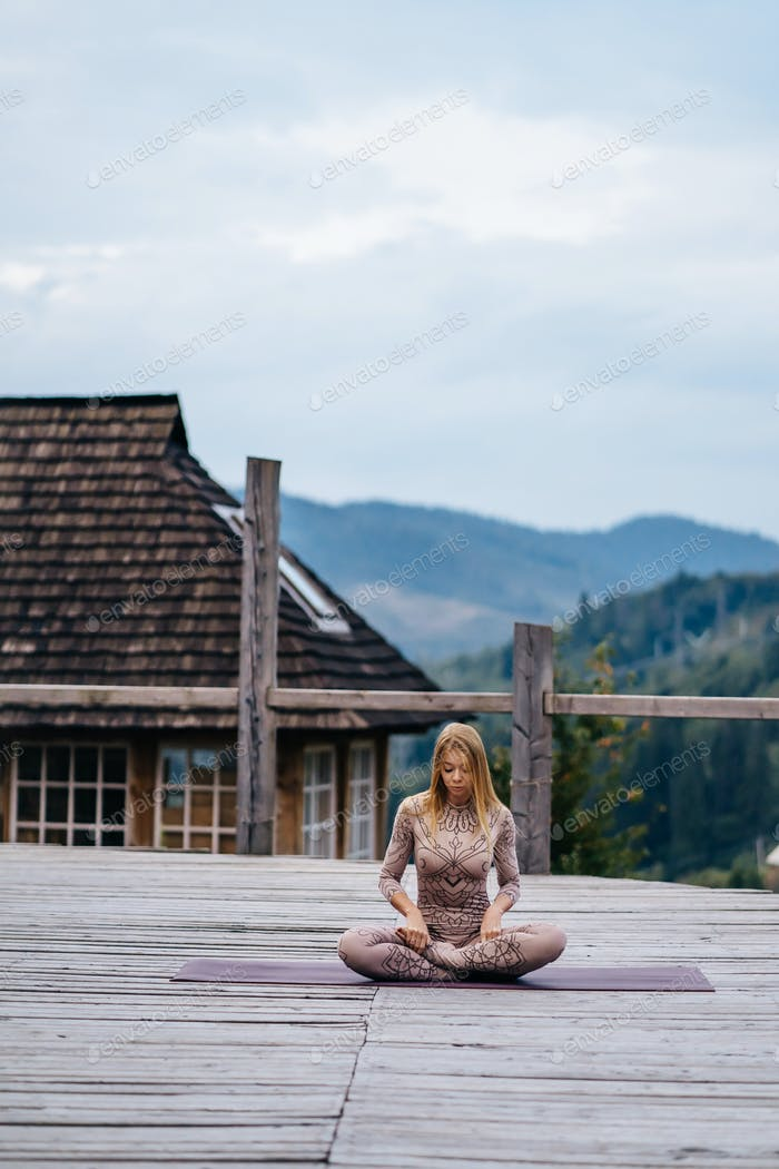 A woman sitting in lotus position at the morning on a fresh air