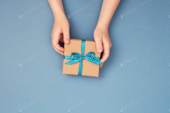 Childs Hands Holding Gift Box on Blue Background.