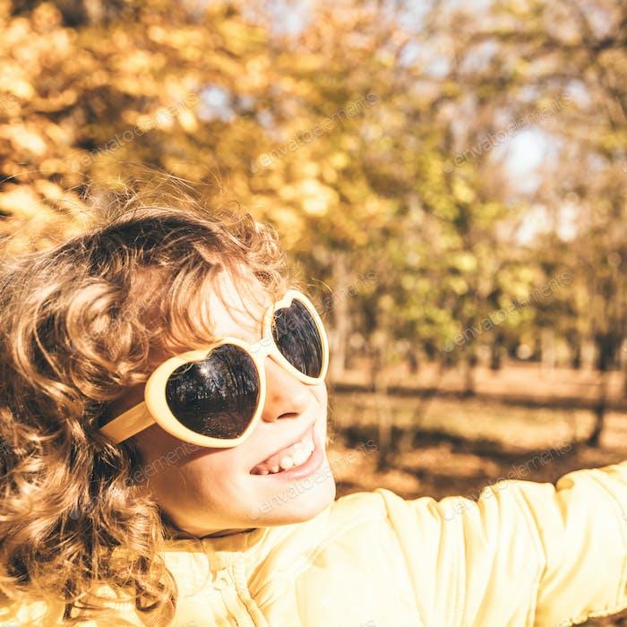 Glückliches Kind mit Spaß im Freien im Herbstpark