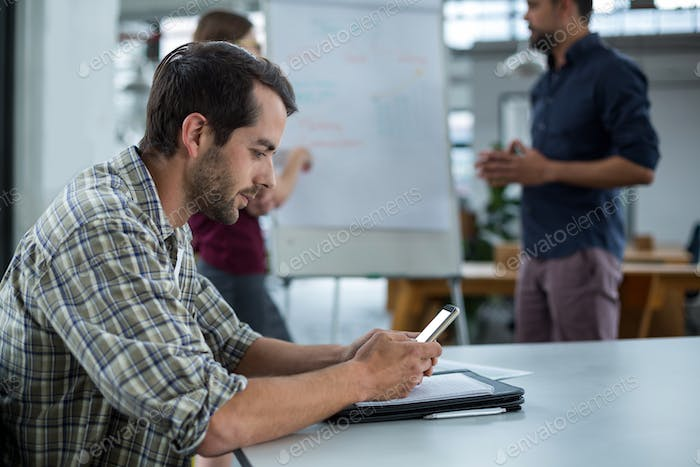 Business executive using mobile phone in a meeting