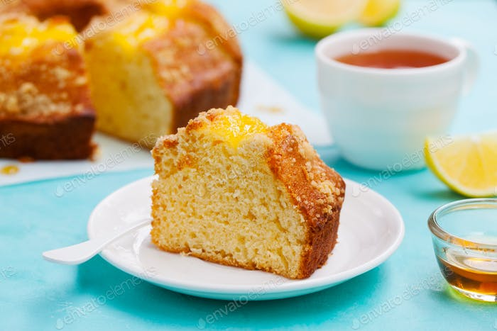 Lemon Bundt Cake with Cup of Tea. Blue Background. Close up.
