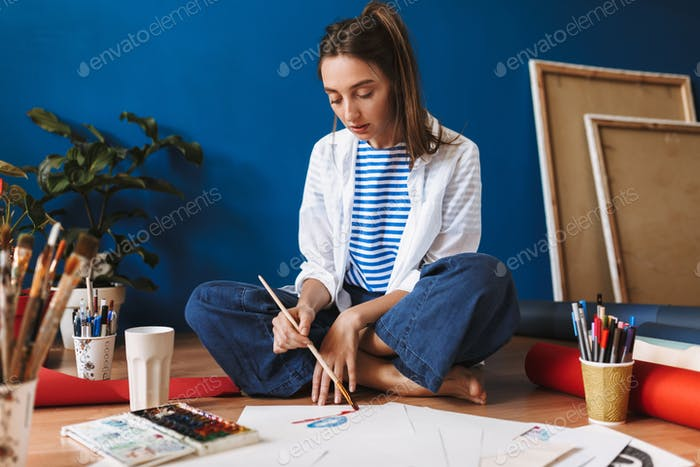 Pensive girl in white shirt and striped T-shirt sitting on floor
