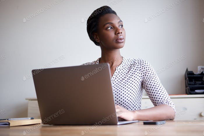 beautiful serious woman sitting at desk with laptop