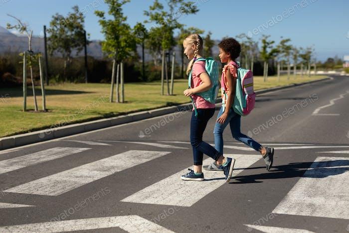 Schoolgirls crossing the road on a pedestrian crossing