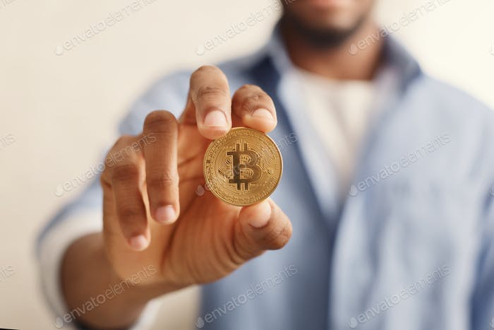 Golden bitcoin in african-american man hand closeup