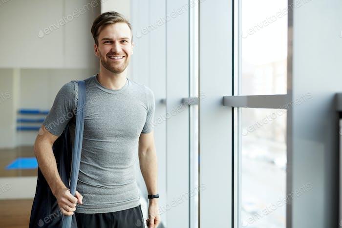 Fröhlicher Mann mit Yogamatte Tasche