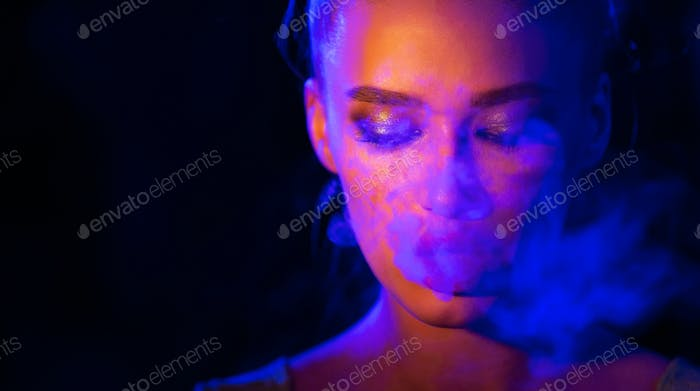 Mysterious girl smoking e-cigarette in neon blue and orange light