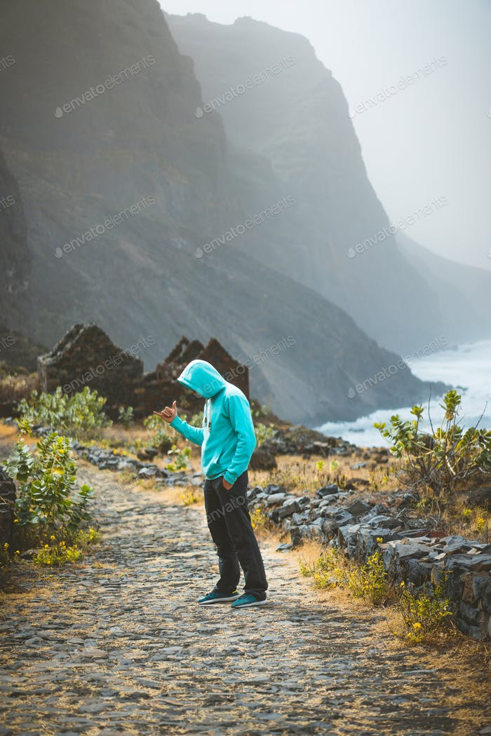 Tourist in hoodie in Aranhas valley hiking to Ponta do Sol. Huge mountains of coastline and old