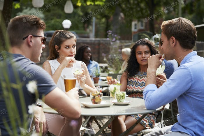 Friends Sitting At Table In Pub Garden Enjoying Drinks Together