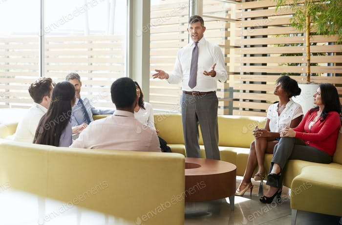 Male manager addressing colleagues in a lounge meeting area