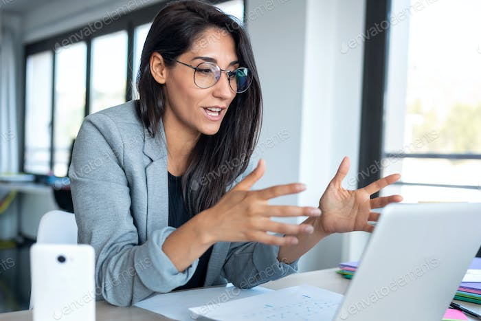 onfident business woman looking and speaking through the webcam while making a video conference