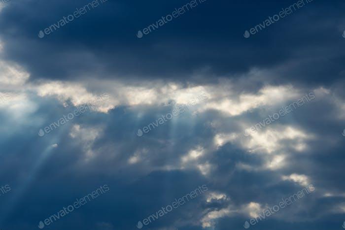 Schöner Sonnenstrahl und bewölkt in blauem Himmel