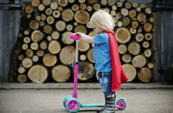 Superhero Baby Boy mit Scooter Adorable Konzept