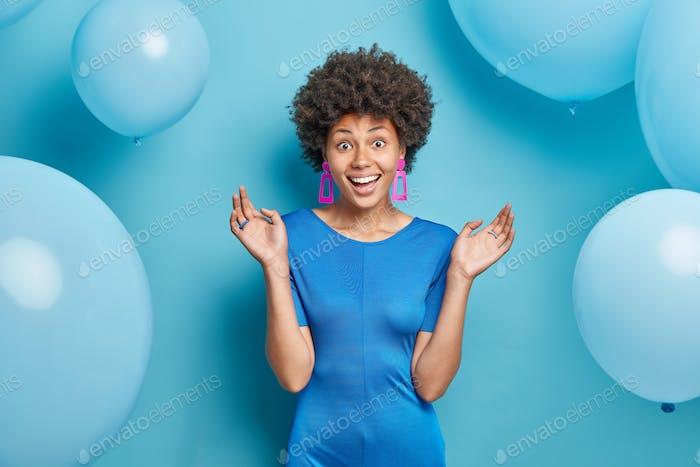 Half length shot of cheerful Afro American lady enjoys festive occasion wears fashionable dress keep