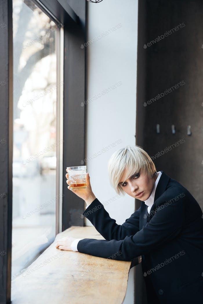 Stylish beautiful blonde drinking at the windowsill