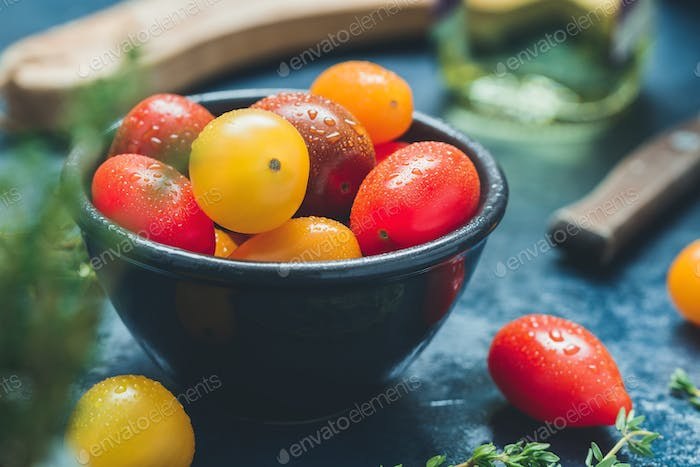 Colorful cherry tomatoes in a black bowl in a kitchen.