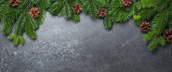Weihnachtlicher Hintergrund mit Tannenzweigen und Zapfen auf Schwarz