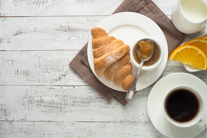 Croissant jam coffee at white wooden table.