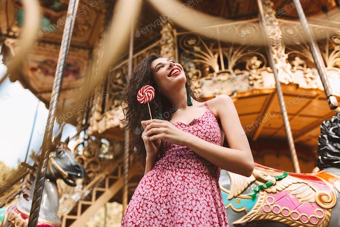 Beautiful lady in dress with lolly pop candy in hands happily looking aside at beautiful carousel