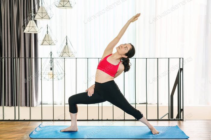 Asian woman practicing yoga from home when Covid19 outbreak and lockdown, healthy