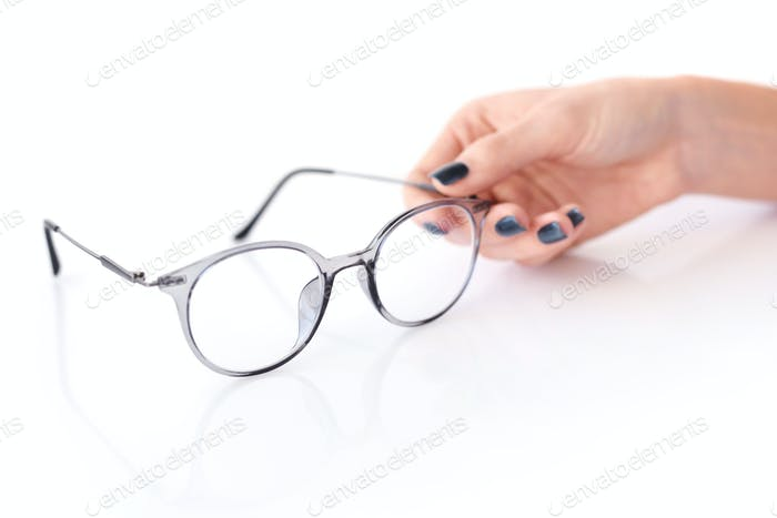 Beautiful glasses whit female hand on white background