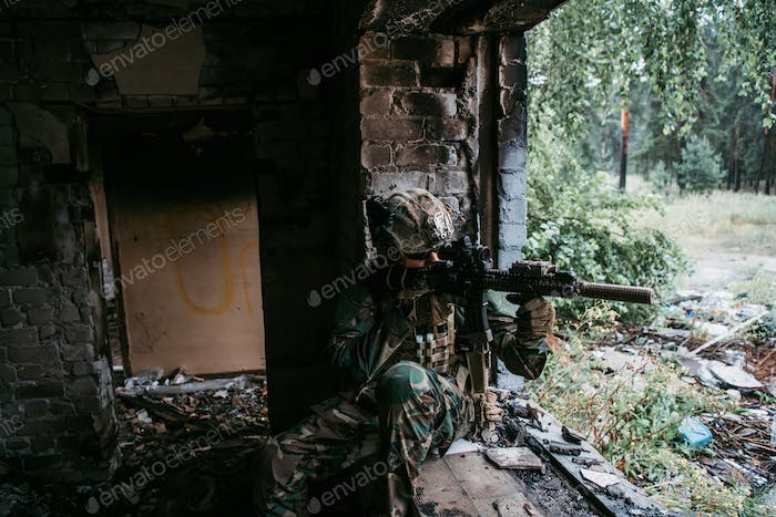 Soldier in camouflage with a military weapon aiming through the rifle sight through the window of an