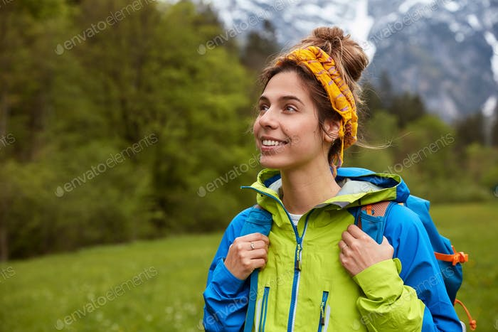 Relaxation, nature and tourism concept. Tourist girl with satisfied facial expression, strolls on me