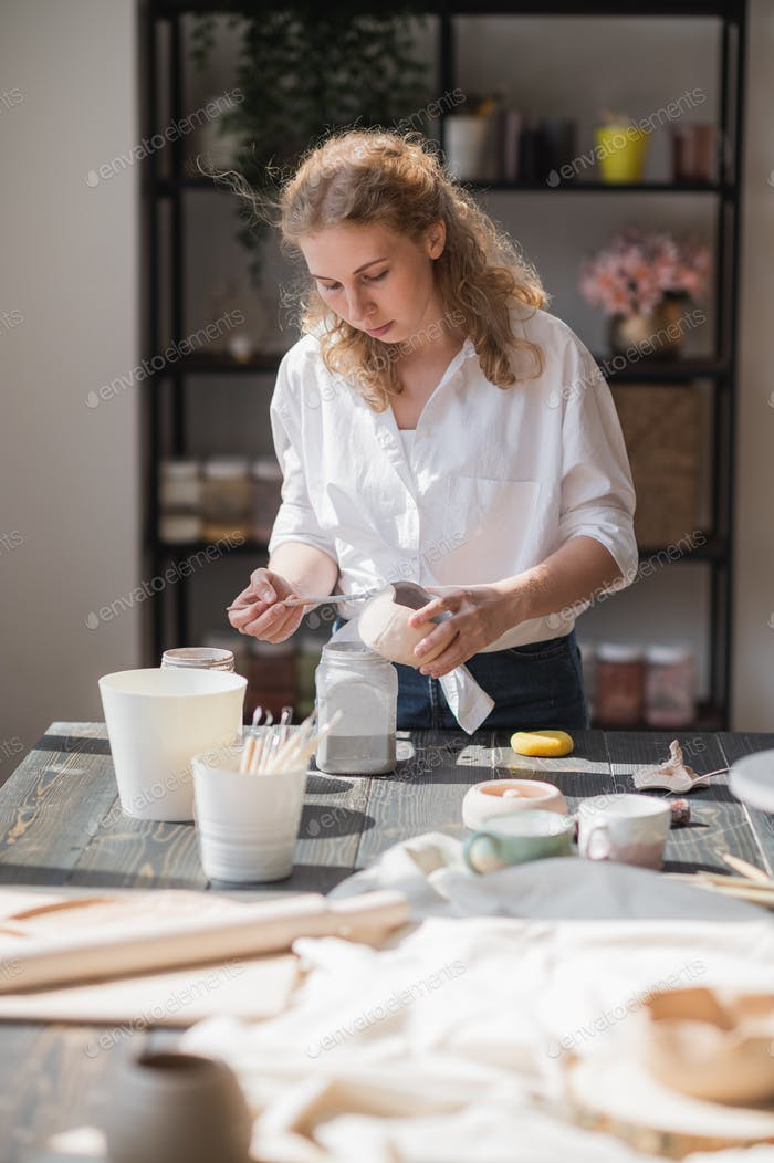 Close up of a woman making ceramic and pottery tableware at the workshop, working with clay and