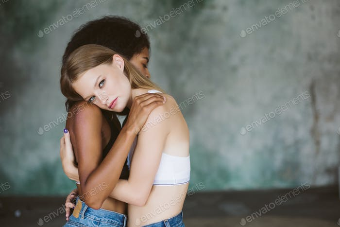 Young attractive woman with blond hair in top hugging african am
