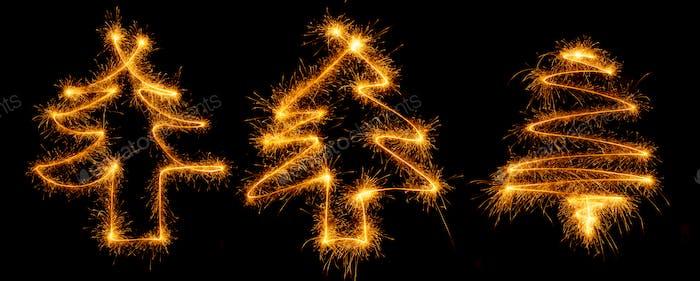 Three christmas tree made by sparkler on a black