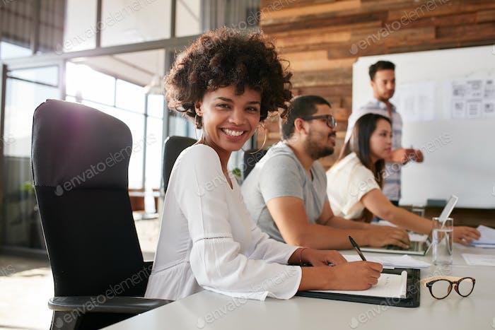 Junge afrikanische Frau sitzt auf einer Business-Präsentation