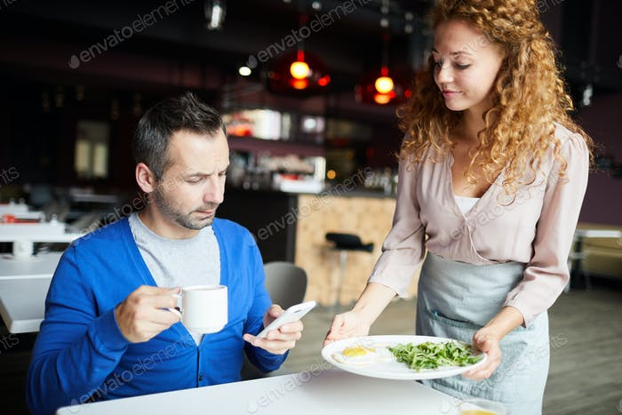 Busy man answering text message in restaurant